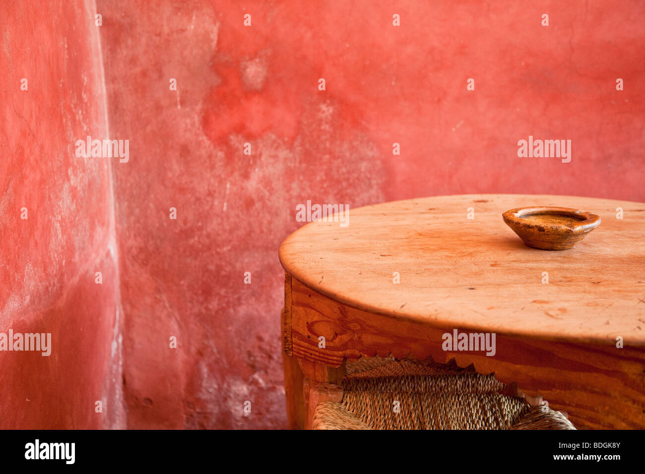 Small table, ash tray and stool in a Moroccan café with a bright red wall - Stock Image