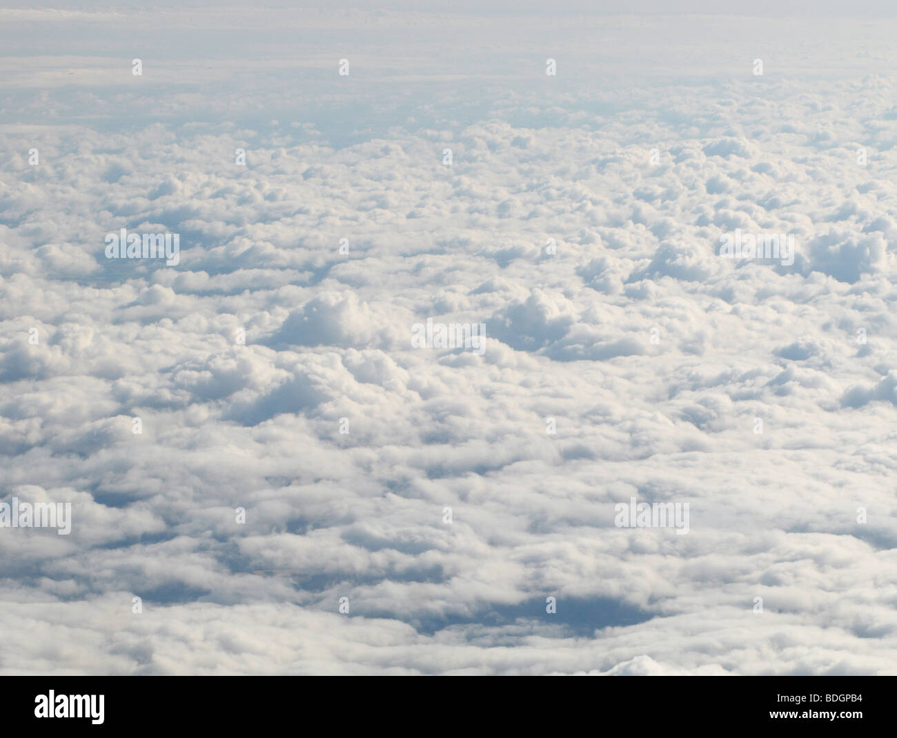 Early morning sunlight hitting a blanket of clouds shot from above - Stock Image