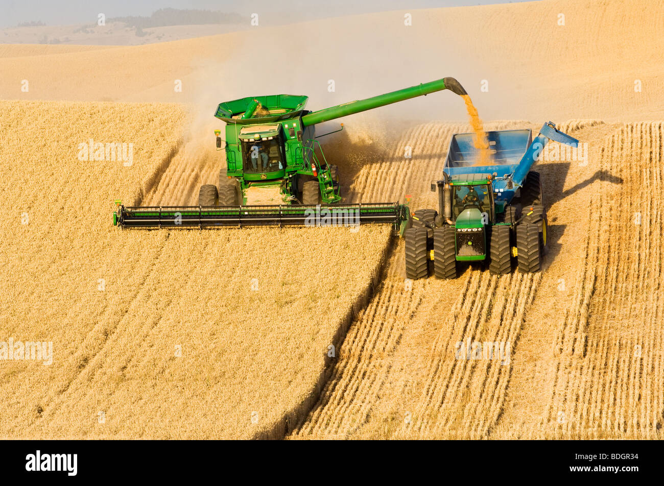 "A John Deere combine harvests Soft White wheat on rolling hillside terrain and unloads into a grain wagon ""on-the - Stock Image"