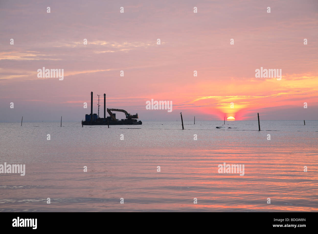 Sunrise over the Sound - Øresund - between Denmark and Sweden with dredger at anchor. Ambience. Stock Photo