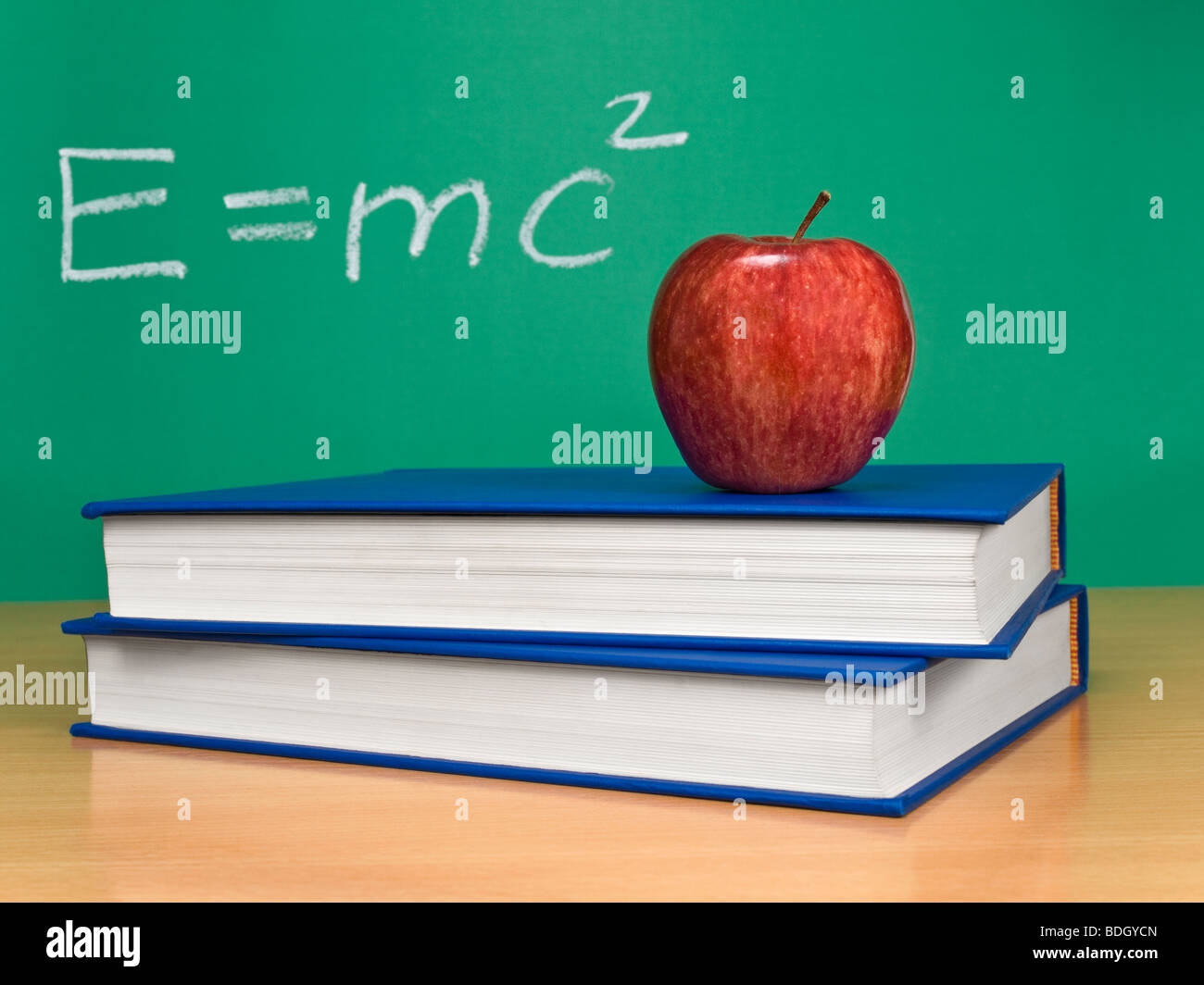Einsteins formula of theory of relativity on a chalkboard. An apple over books on foreground. - Stock Image