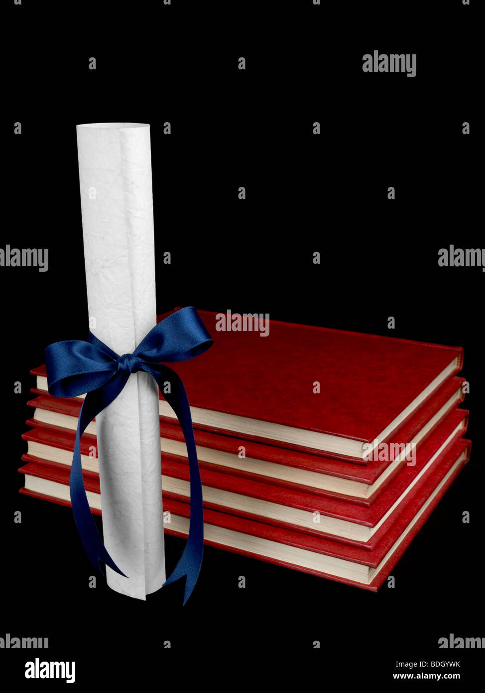 A diploma with blue ribbon and several books aside. Isolated on black. - Stock Image