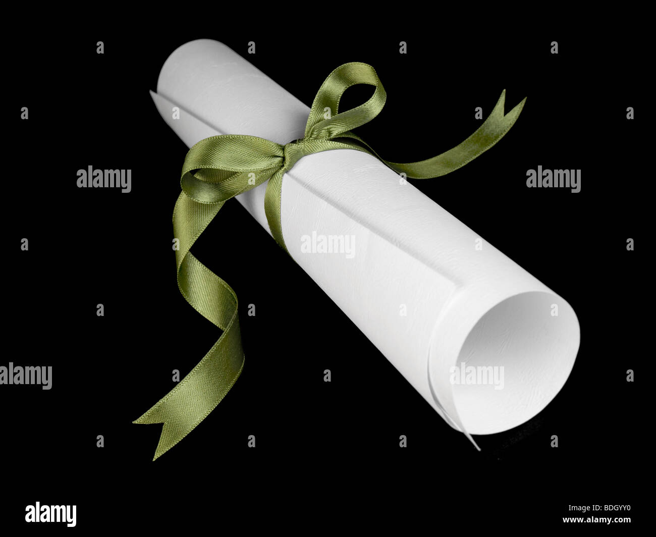 Diploma with a green silk ribbon, isolated on black background. Stock Photo