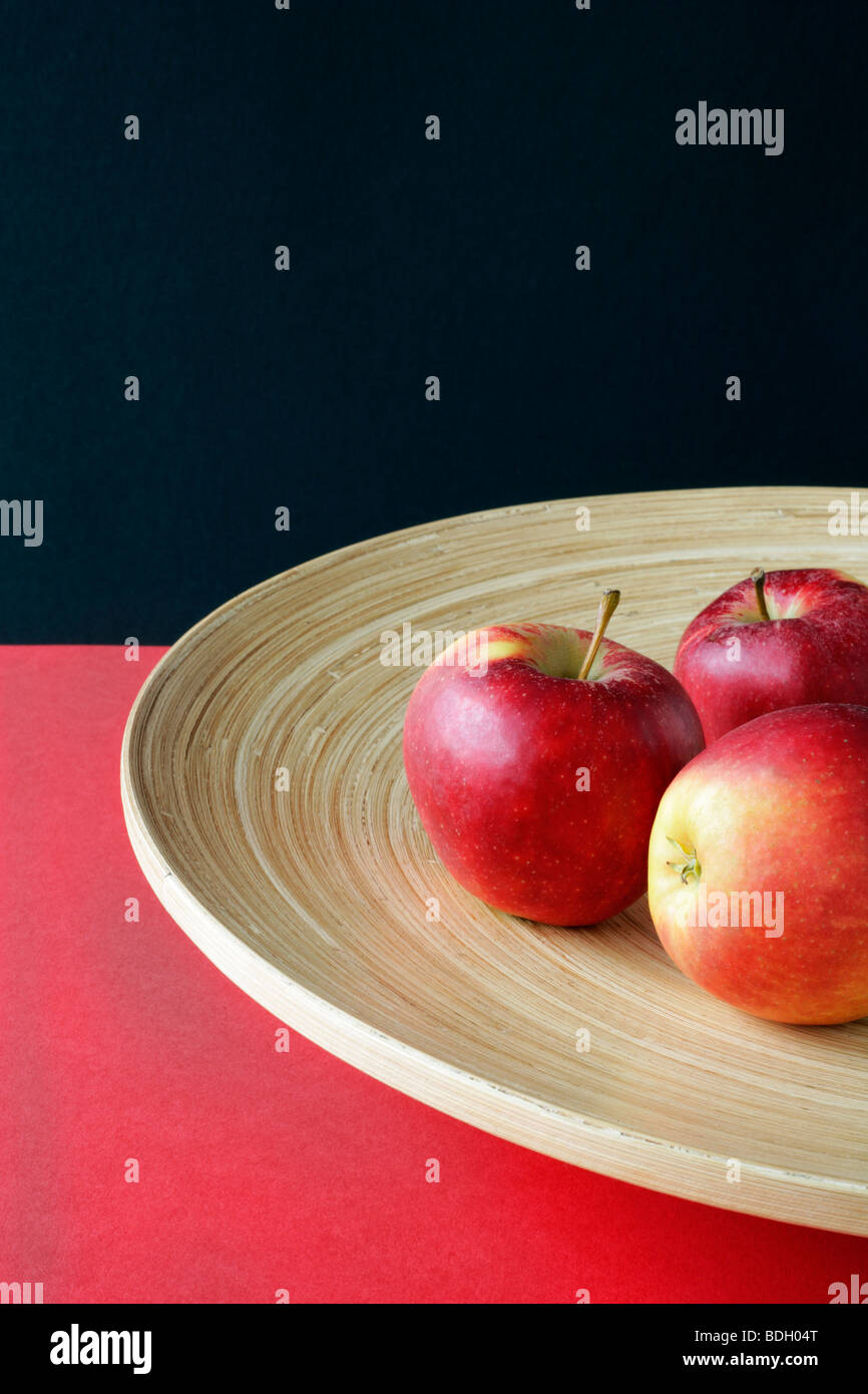 Three red apples in a bright timber shell Stock Photo