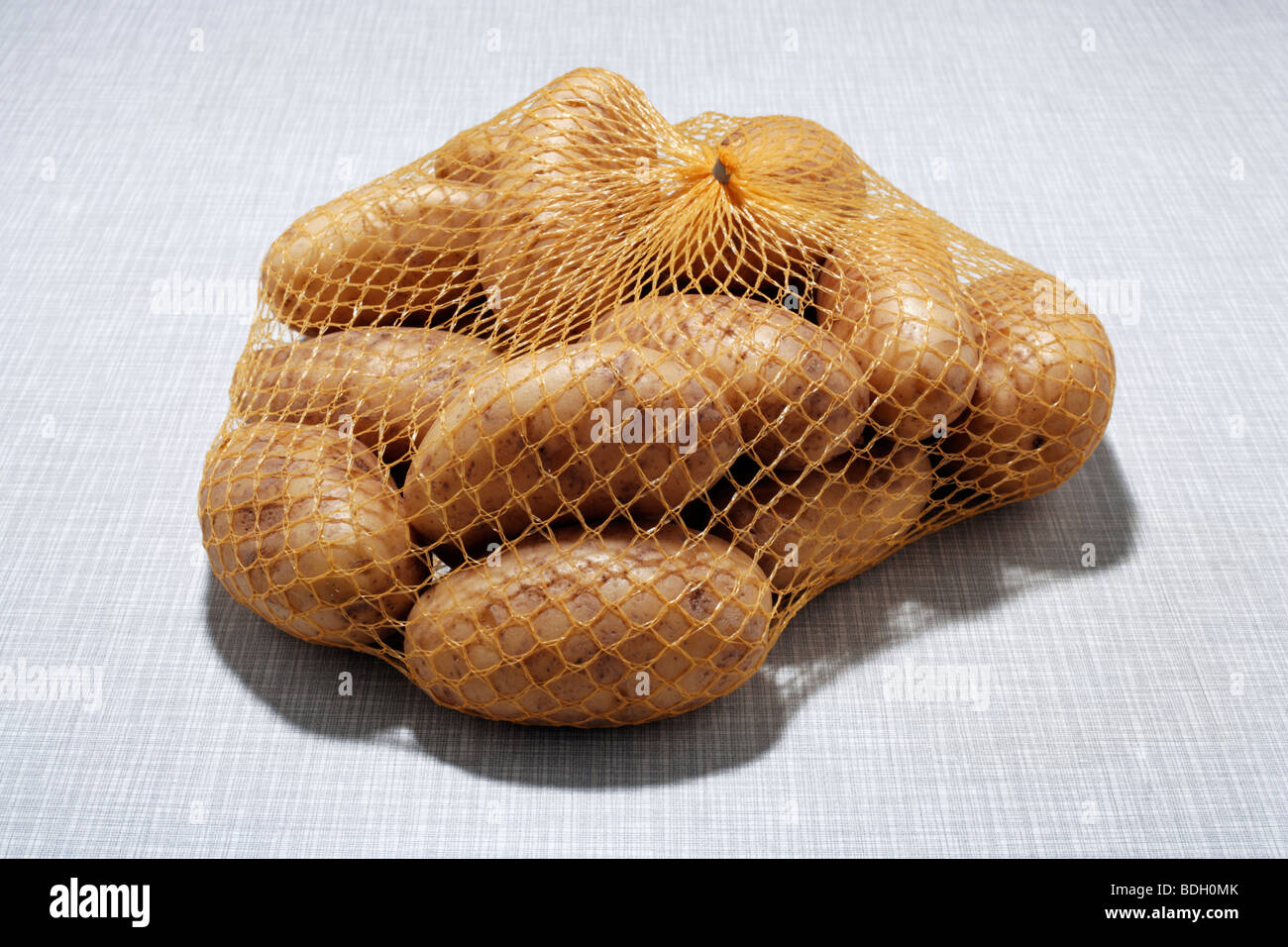 Potatoes in the net on kitchen desk top - Stock Image