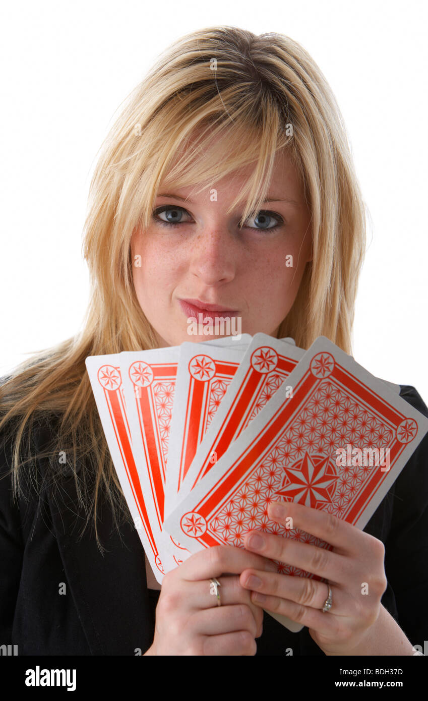 young 20 year old blonde woman holding five large playing cards with wry smile - Stock Image