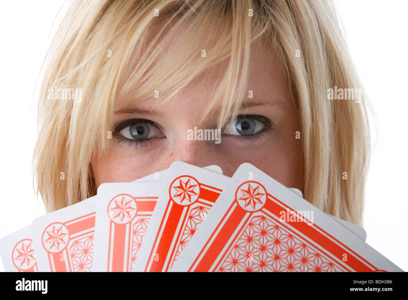 young 20 year old blonde woman holding five large playing cards over her face - Stock Image