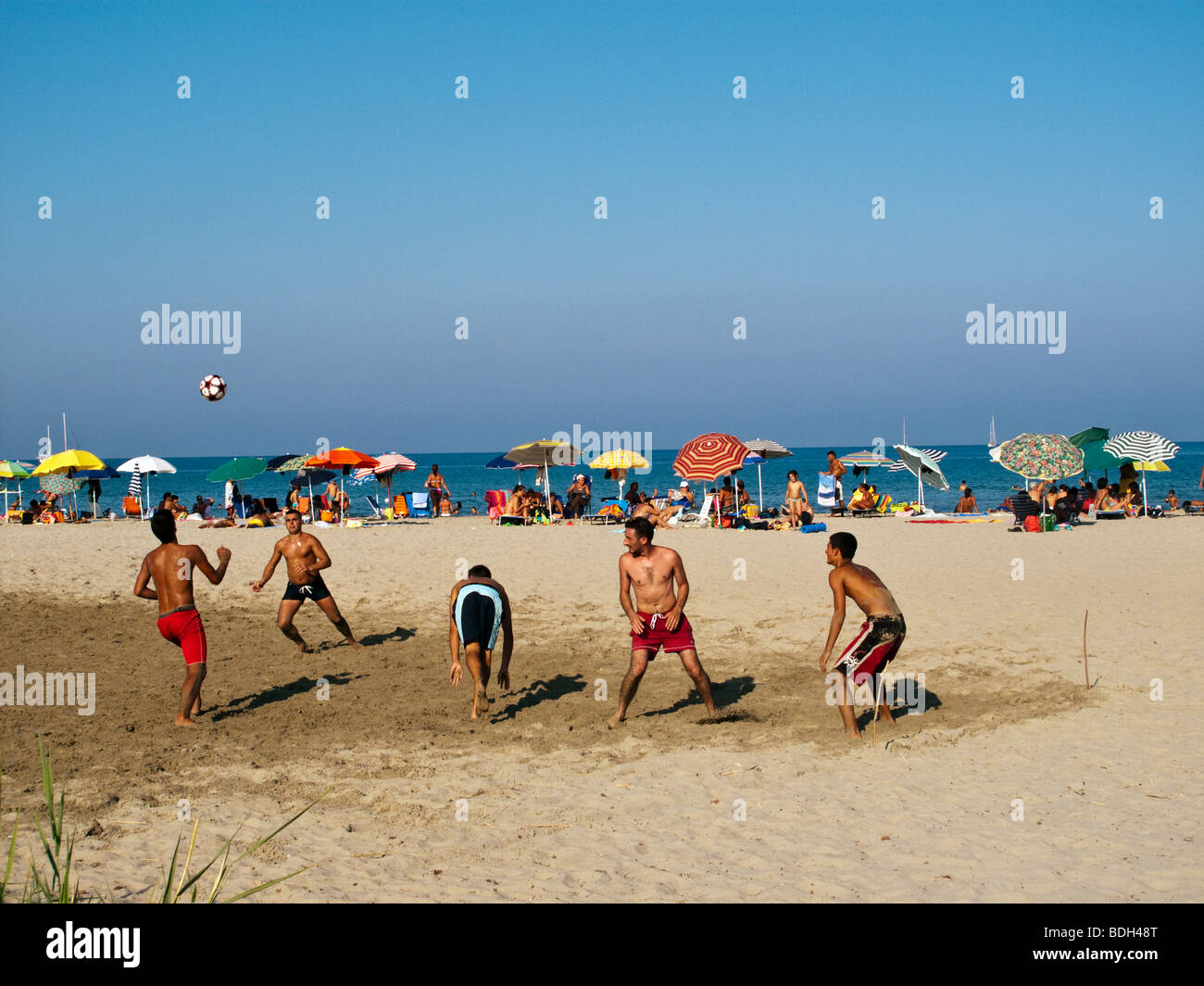 Young men playing football on Tertenia Beach - Stock Image