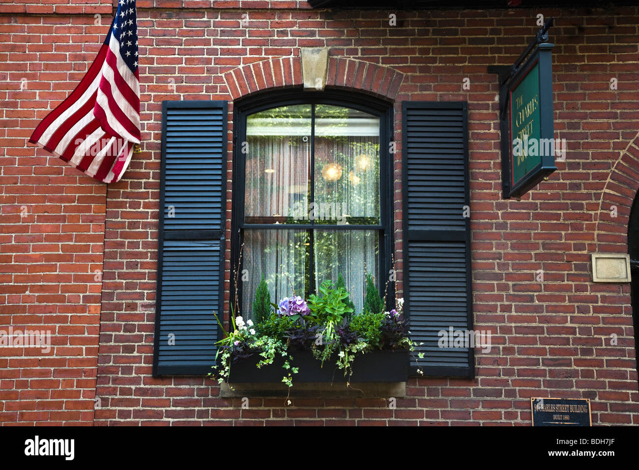 Flower box and American Flag of the CHARLES STREET INN - BOSTON, MASSACHUSETTS - Stock Image