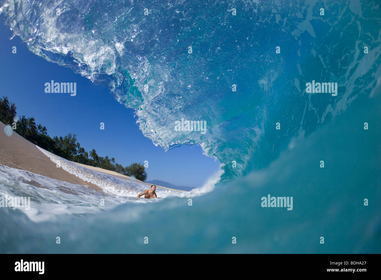 A young man about to be hit by wave at Keiki Beach on the North Shore of Oahu, Hawaii. - Stock Image