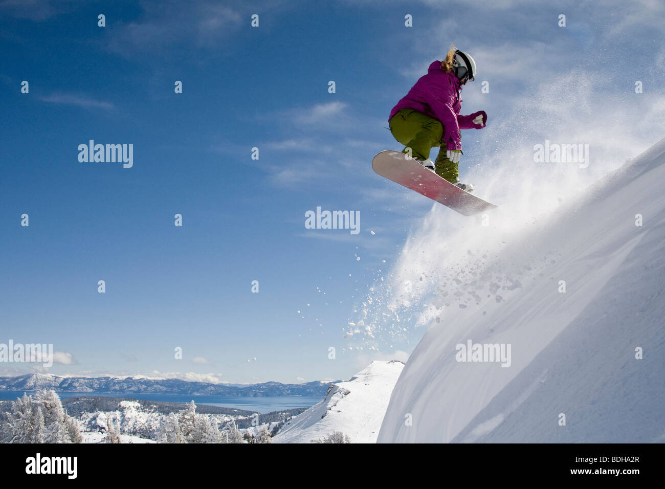 A female snowboarder doing a 540 in the backcountry on a sunny day in California. - Stock Image