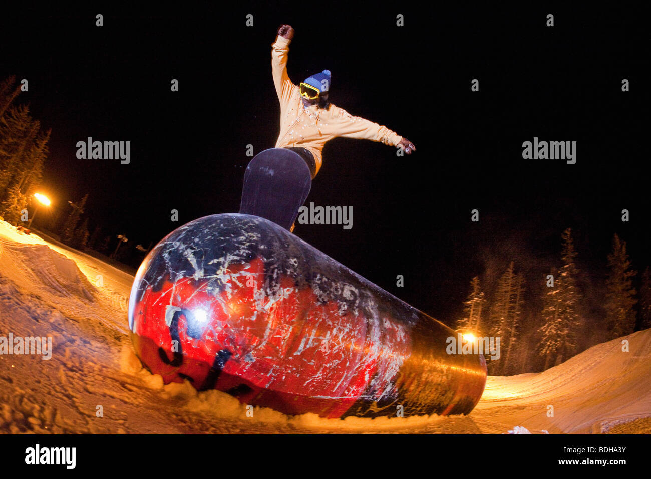 View from below of a snowboarder riding in the board park at night. - Stock Image