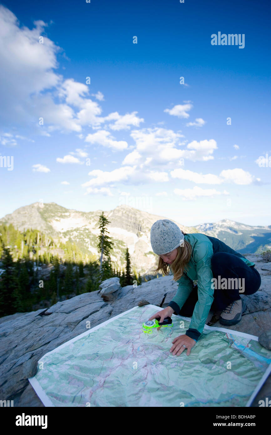 Woman using a map and compass while backpacking in the Montana mountains. Stock Photo