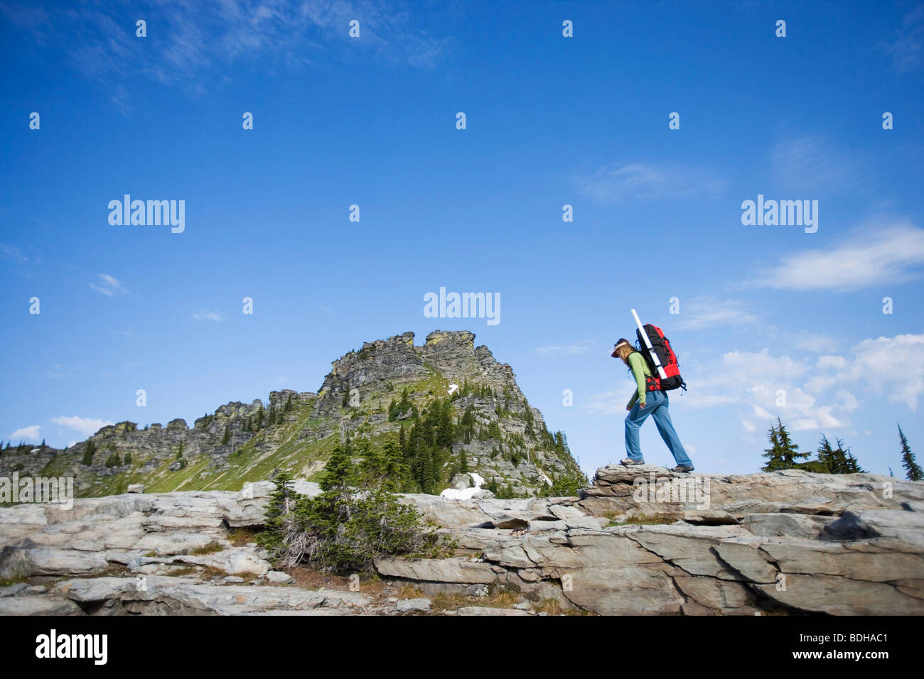 Woman backpacking in a wilderness area under a bright blue sky. - Stock Image