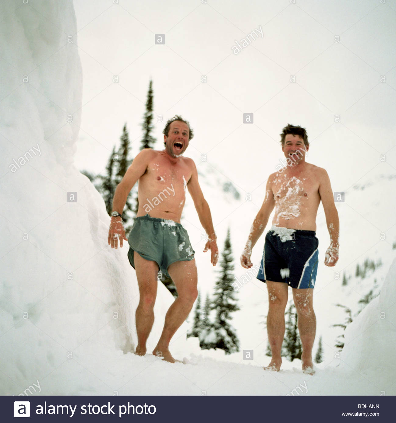 Two men stand covered in snow wearing only swimming suits at a backcountry ski lodge in British Columbia, Canada. - Stock Image