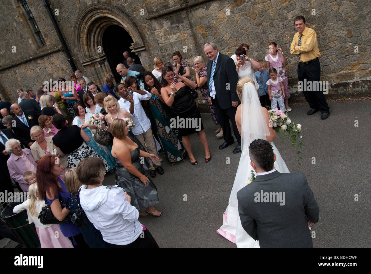 bride and groom and guests outside church - Stock Image