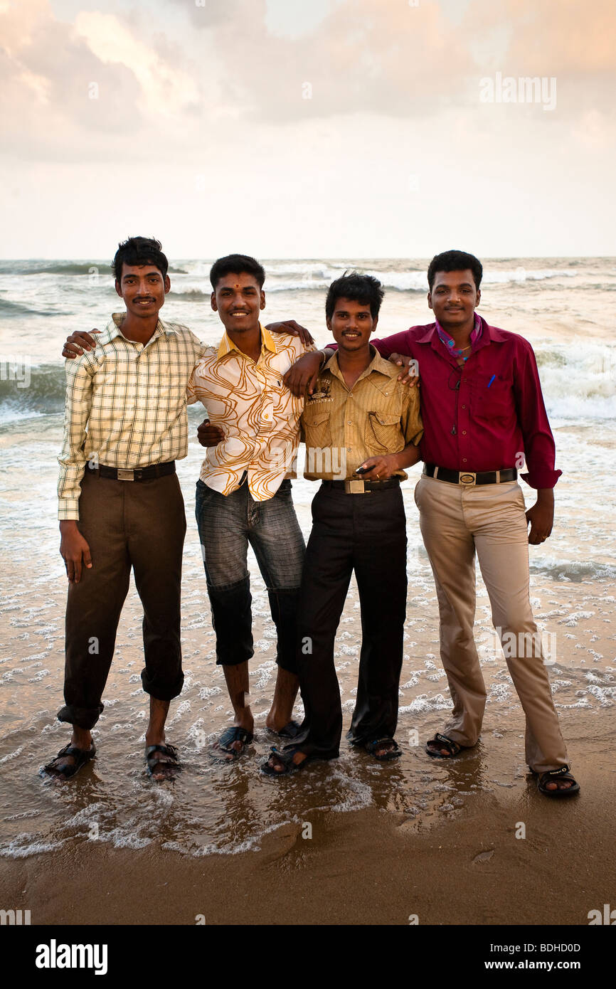 Four smiling young men stand for a portrait on a beach. - Stock Image
