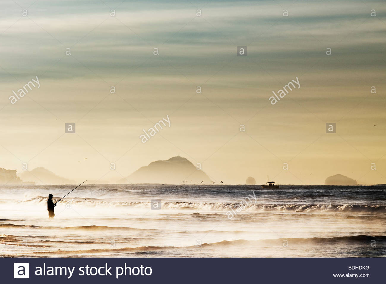 Fisherman fishing standing in the Pacific Ocean no model release required as figure silhouette totally unrecognizable - Stock Image