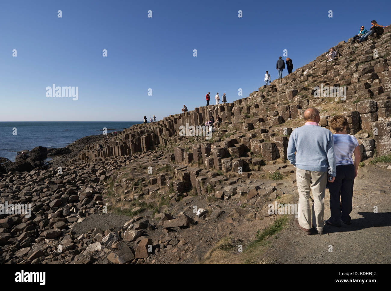 A couple studying the rock formations at the Giant's Causeway. - Stock Image