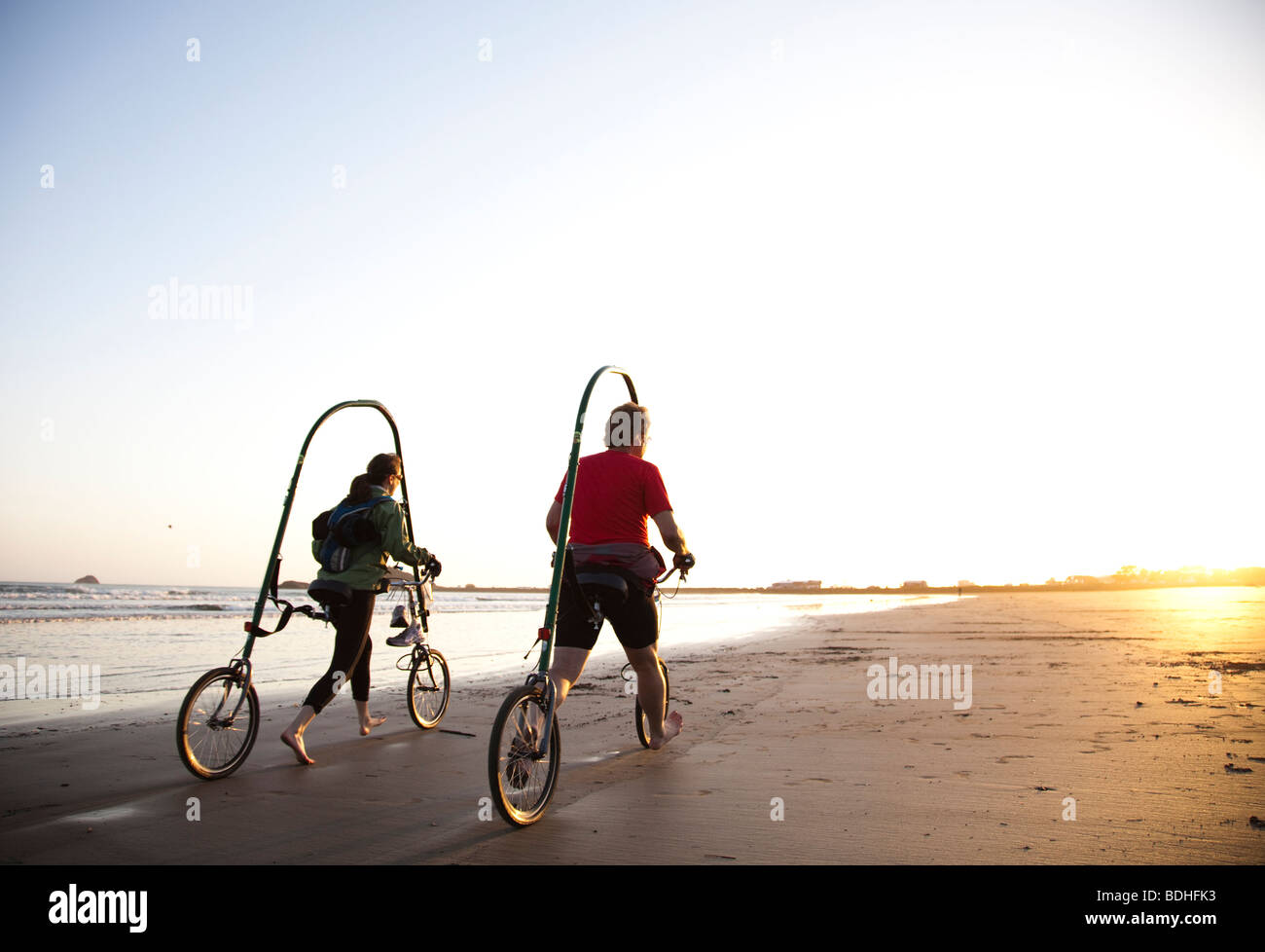 A new form of bicycle is tested on the beach at sunset. - Stock Image