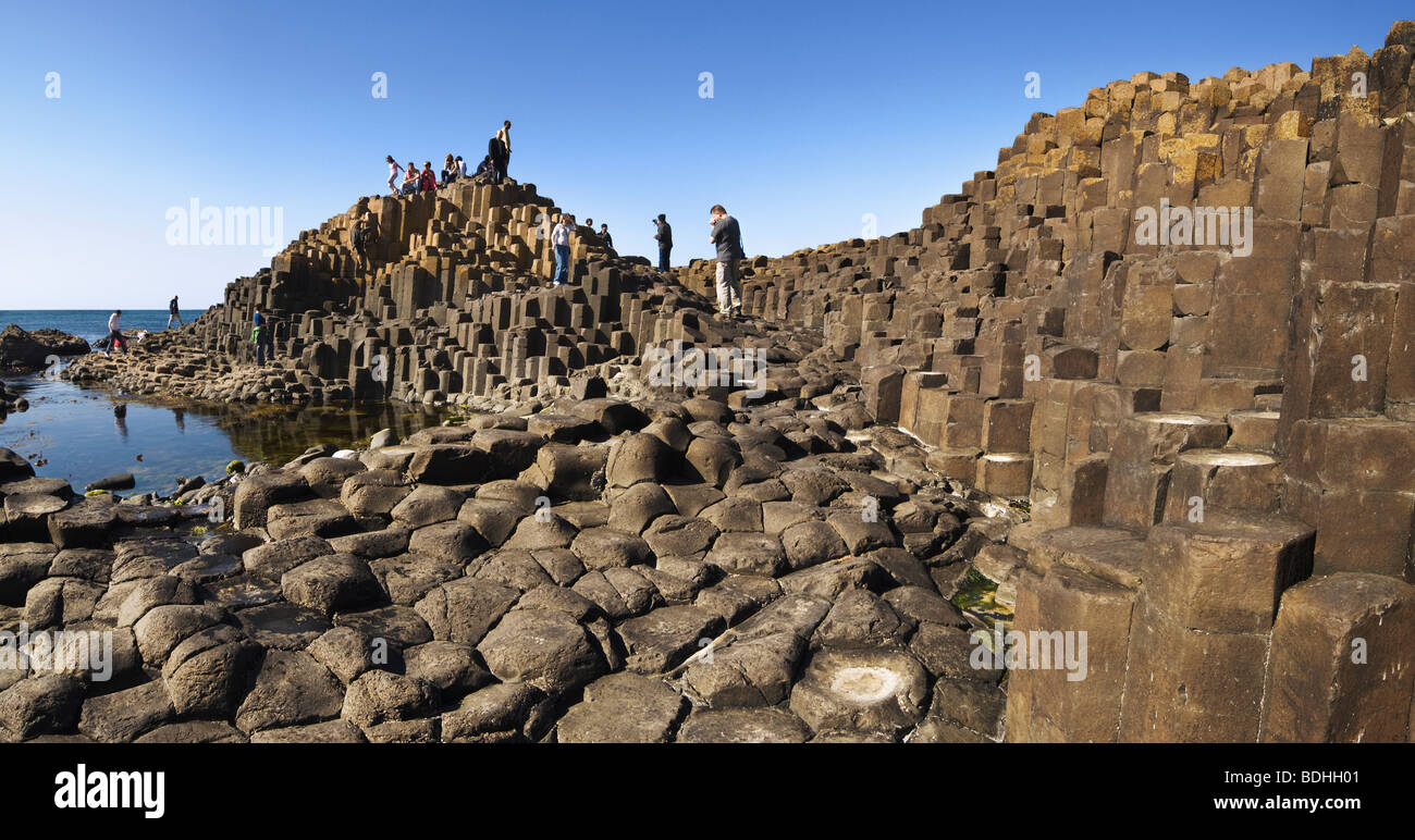 Tourists exploring the rock formations of the Giants Causeway. - Stock Image