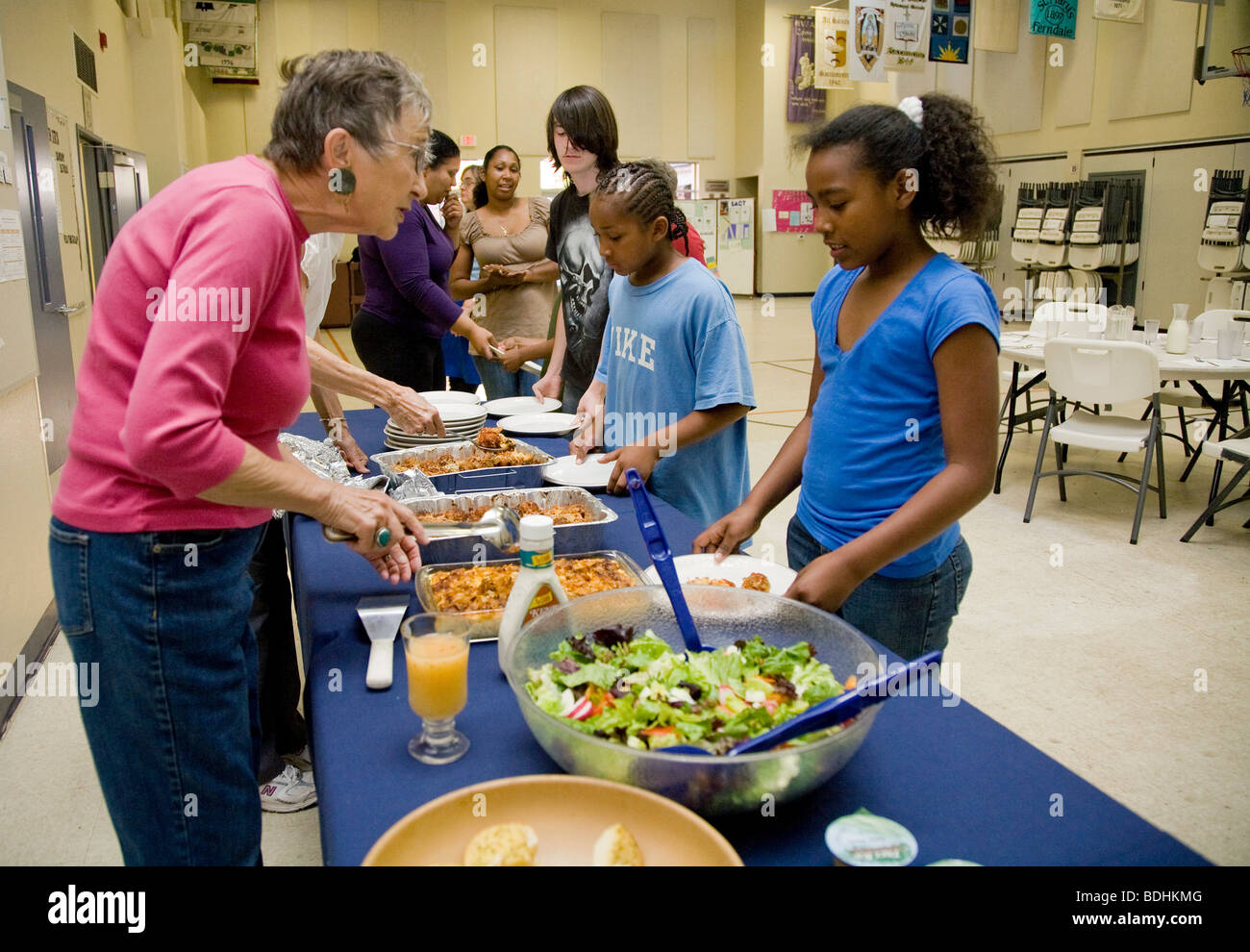 Selena Pina, a homeless mother of four and her children stand in line to receive dinner prepared by volunteers of Stock Photo