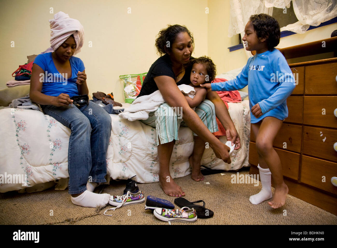 Selena Pina, a homeless mother of four, gets her children dressed for school at the Family Promises Center in Sacramento, Stock Photo