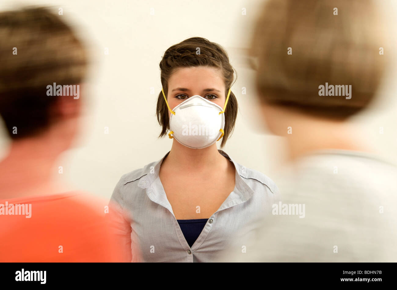 Women with surgical mask protecting against flu / virus transmission - Stock Image