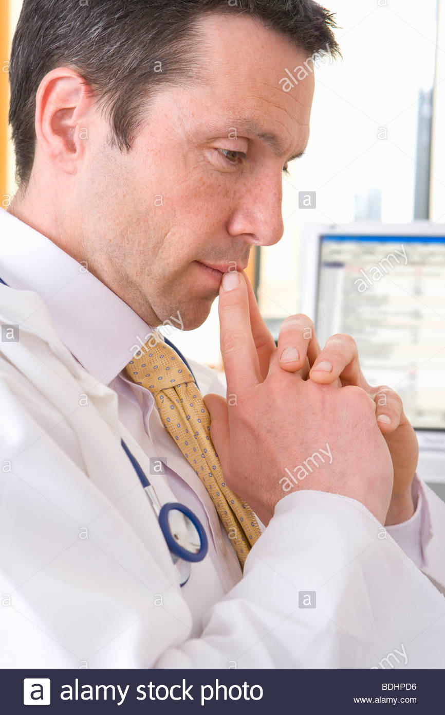 Close up of doctor with hands clasped looking pensive - Stock Image