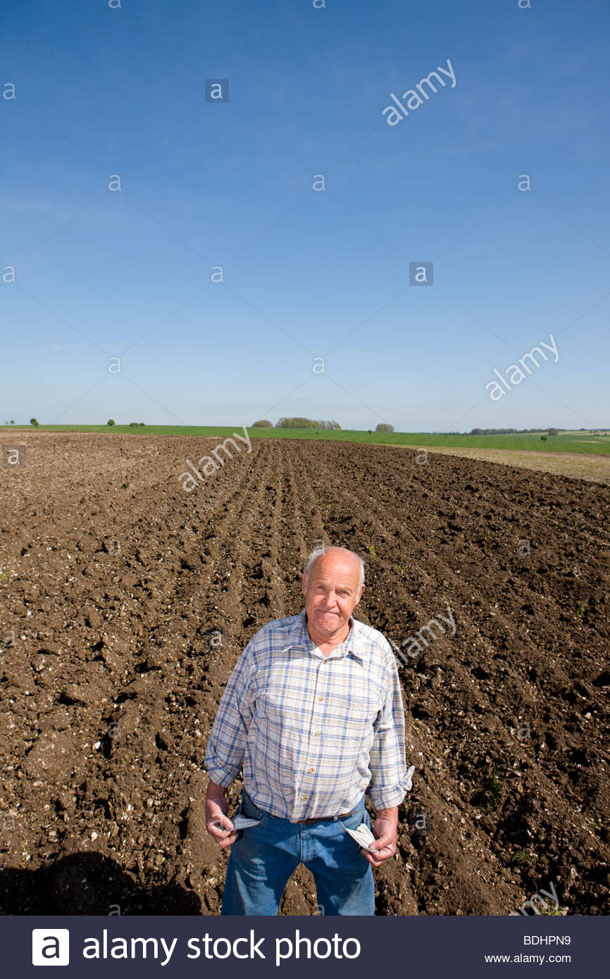 Farmer showing empty pockets in ploughed field - Stock Image