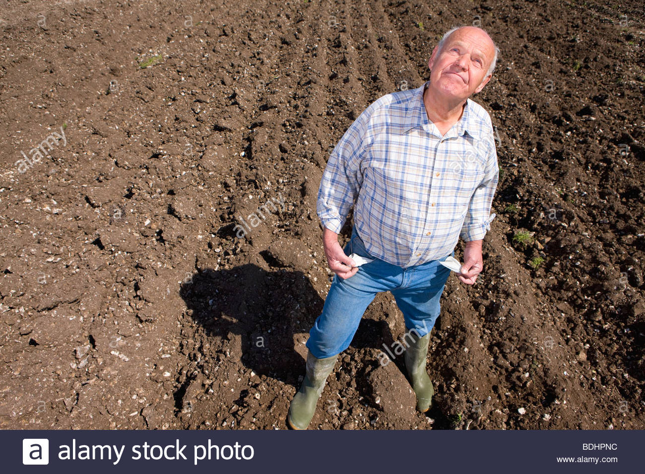 Farmer showing empty pockets and looking up in ploughed field - Stock Image