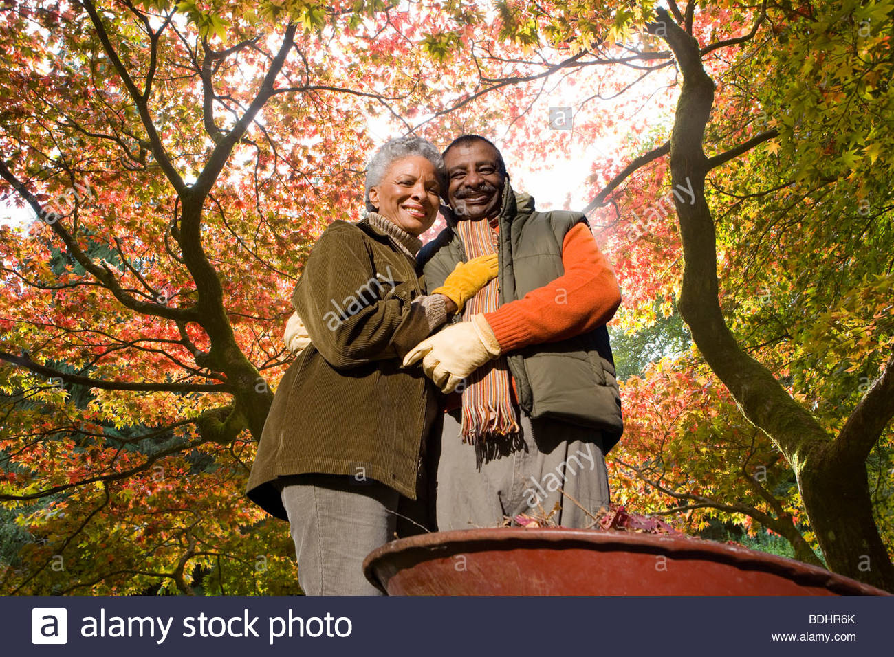 Senior African couple doing yard work in autumn - Stock Image