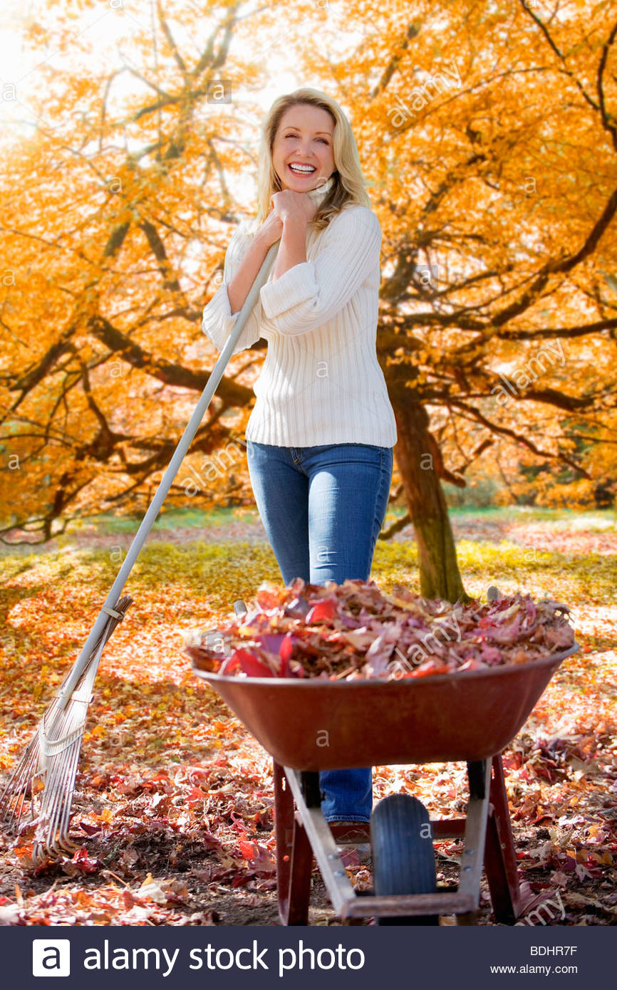 Woman doing  yard work in autumn - Stock Image