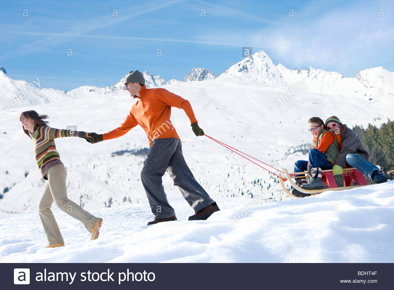 Family pulling sled in the snow - Stock Image