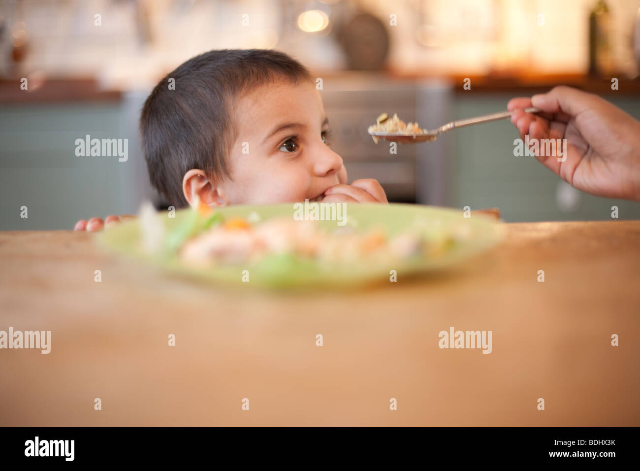 3 year old boy sitting at table with hand holding food on spoon - Stock Image