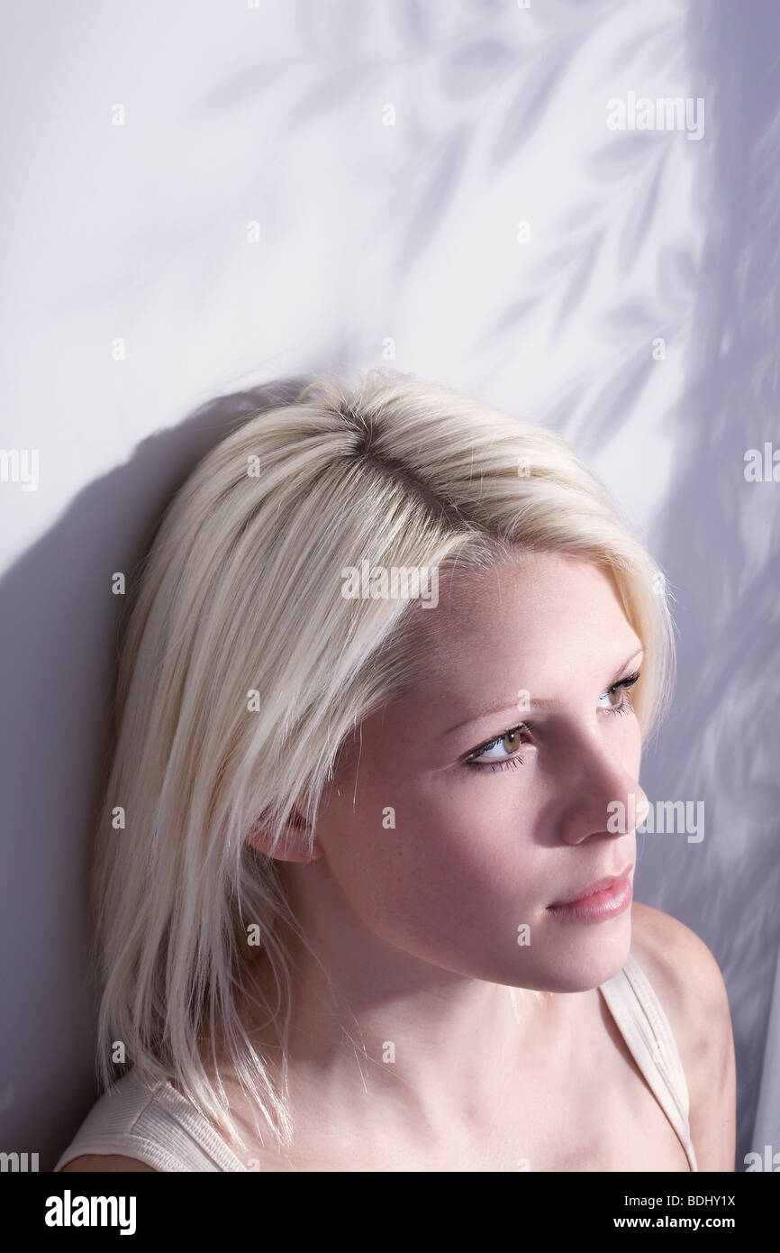 young woman sat in the light from a window, looking off camera - Stock Image