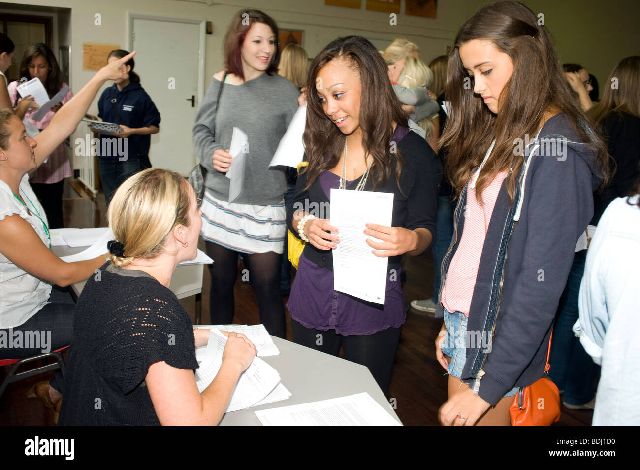 A happy teenage girl clutching her GCSE results - Stock Image