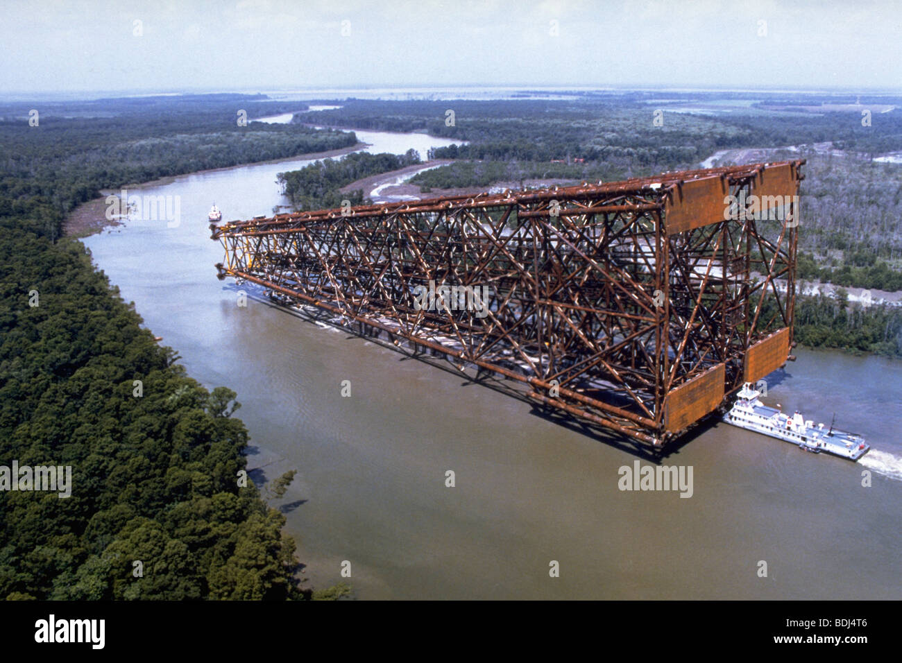 Off shore oil rig, oil jacket being floated down river on barge to gulf of Mexico - Stock Image