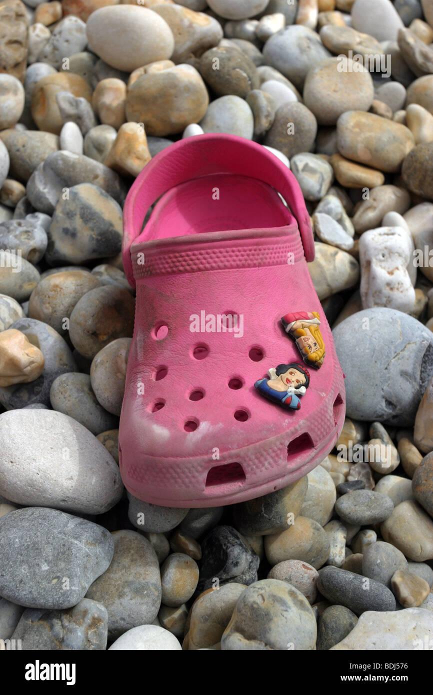 A single croc shoe on a pebble beach - Stock Image