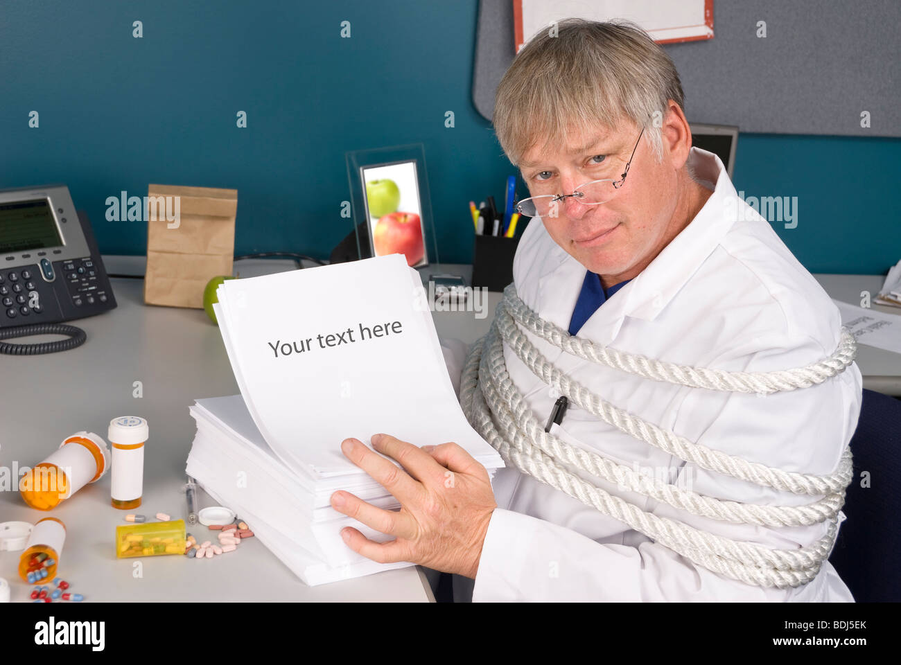 A physician is tied up with a load of bureaucratic paperwork preventing him from doing his job. Stock Photo