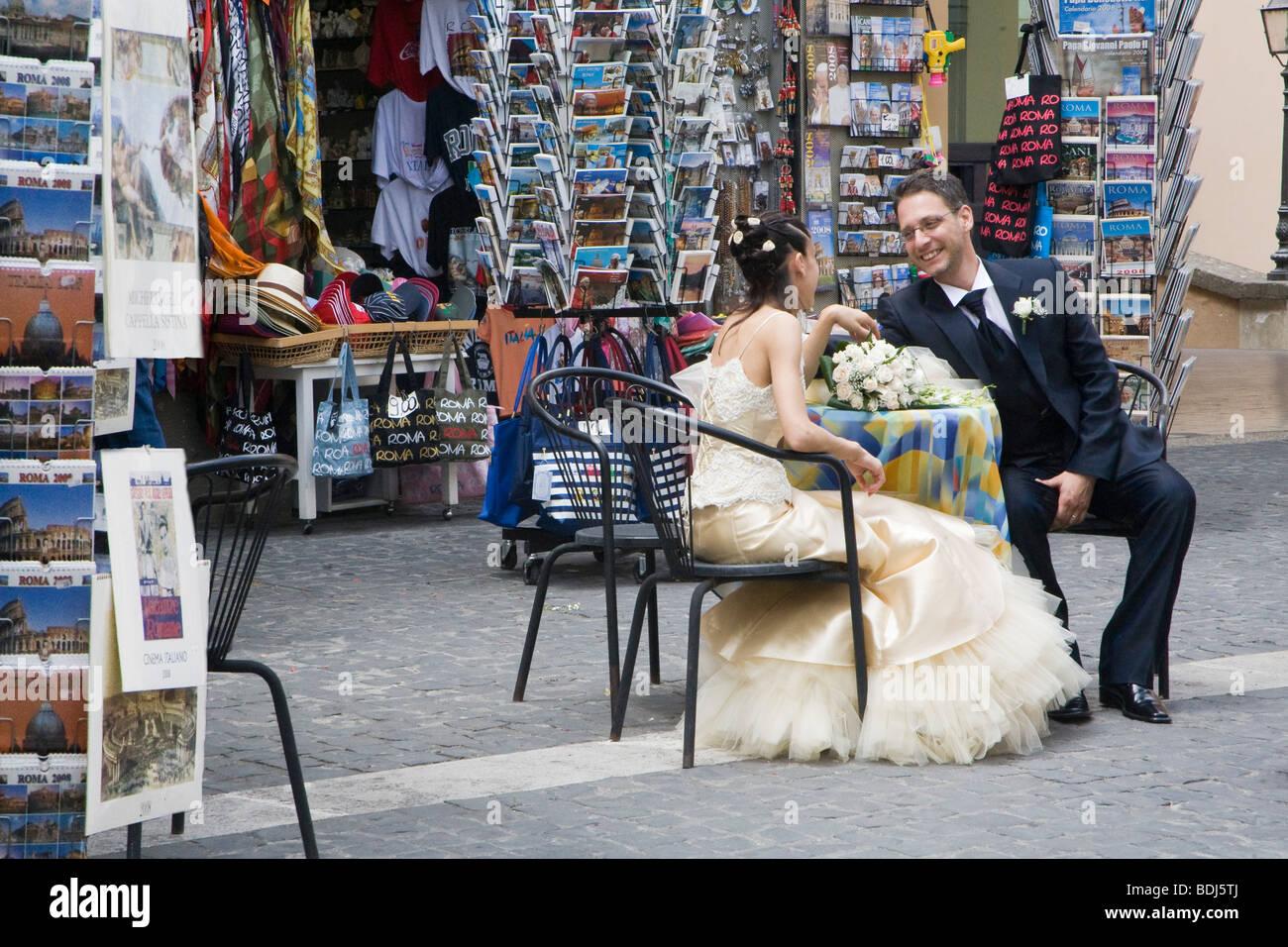 Piazza della Liberta in Castel Gandolfo,wedding couple at a table outside a tourist gift shop, Italy - Stock Image