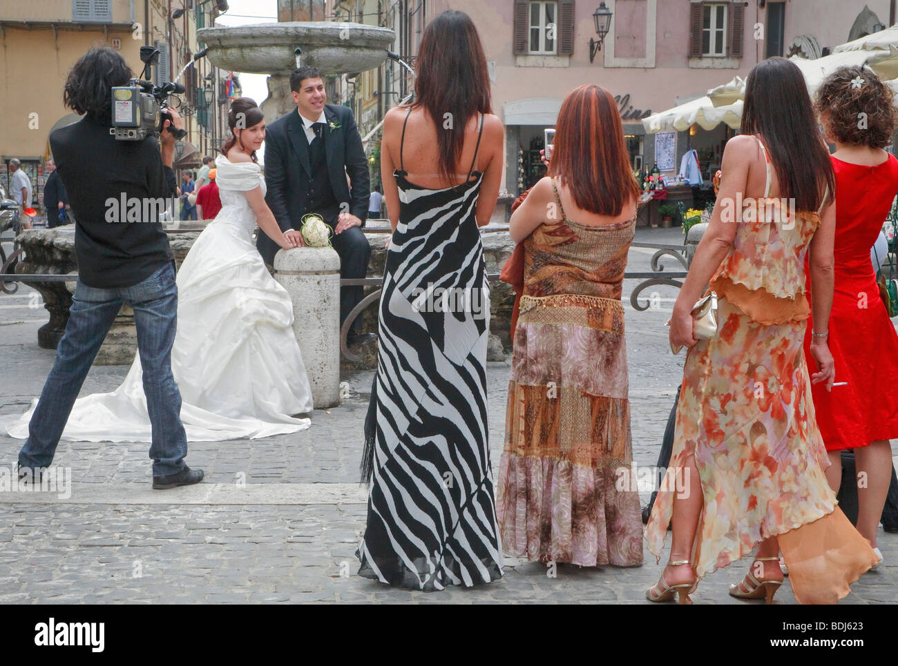 Castel Gandolfo, Piazza della Liberta fountain. lady guests and photographer watch the wedding couple - Stock Image