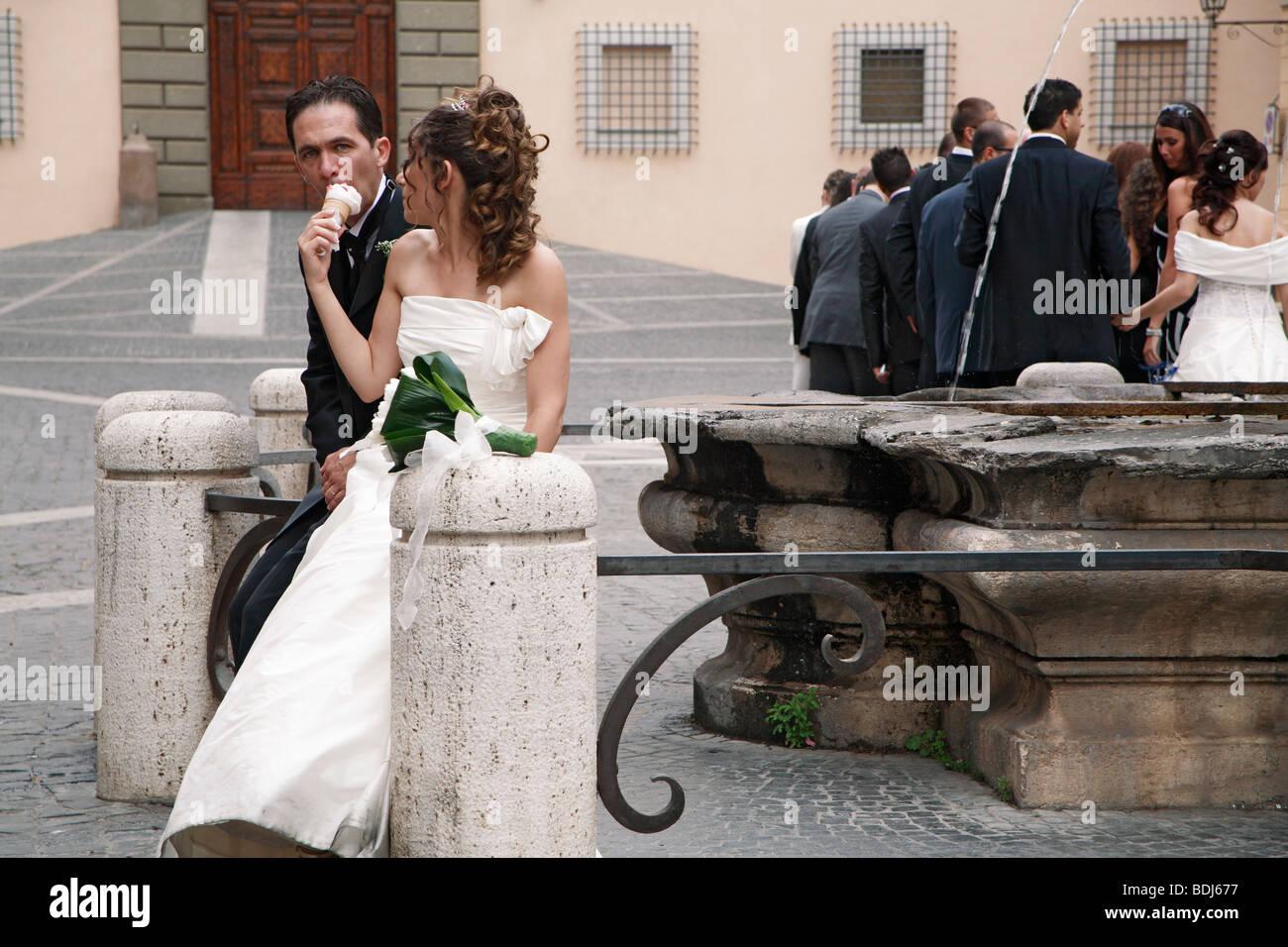 Bride feeding groom a gelato in the Piazza della Liberta, another wedding group in the background Castel Gandolfo, - Stock Image