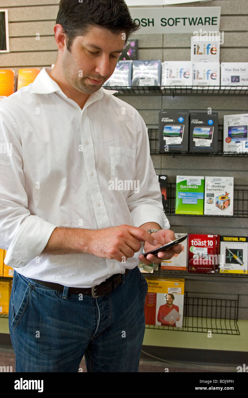 Man using PDA (personal digital assistant) in computer store - Stock Image