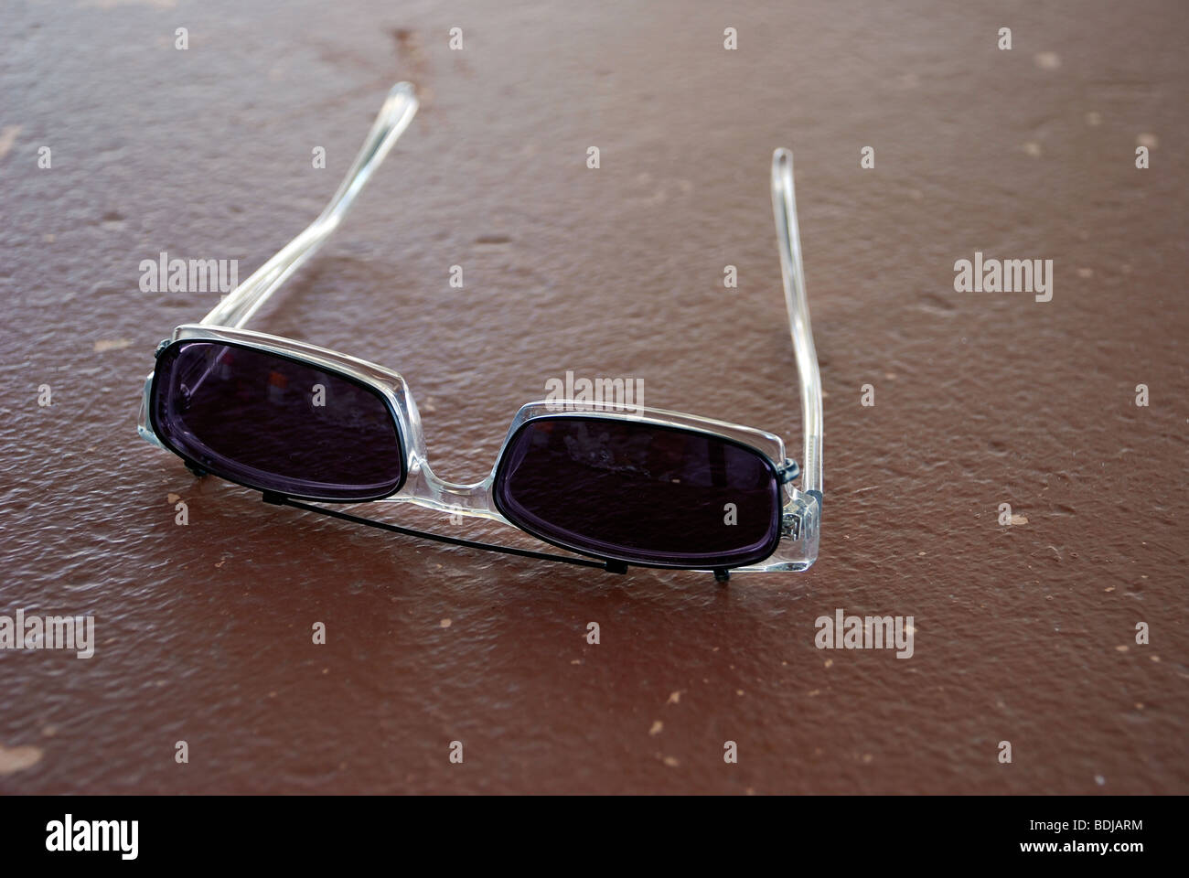 Glasses with sun shade clip-ons on table - Stock Image