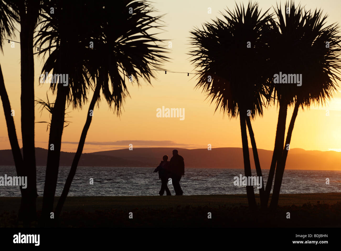 View looking West at sunset across the Firth of Clyde from Largs promenade in Ayrshire, Scotland, UK - Stock Image