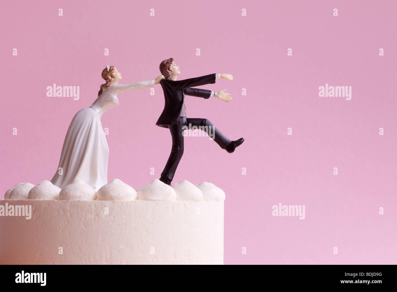 Wedding Cake Figurines, Bride Grabbing Runaway Groom Stock Photo