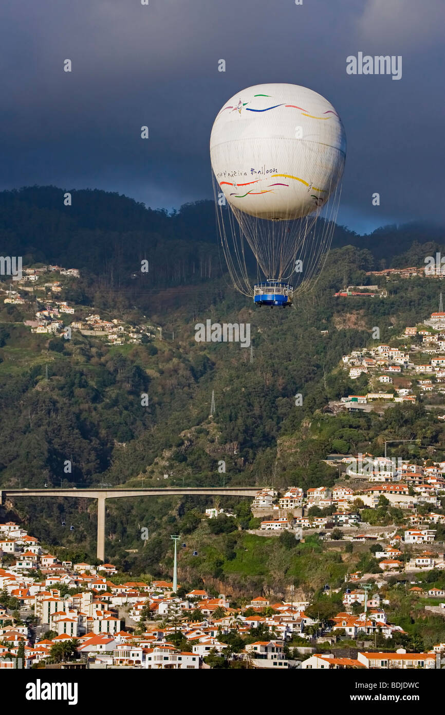 View of a Hot Air Balloon over Funchal Madeira with Dark Skies - Stock Image