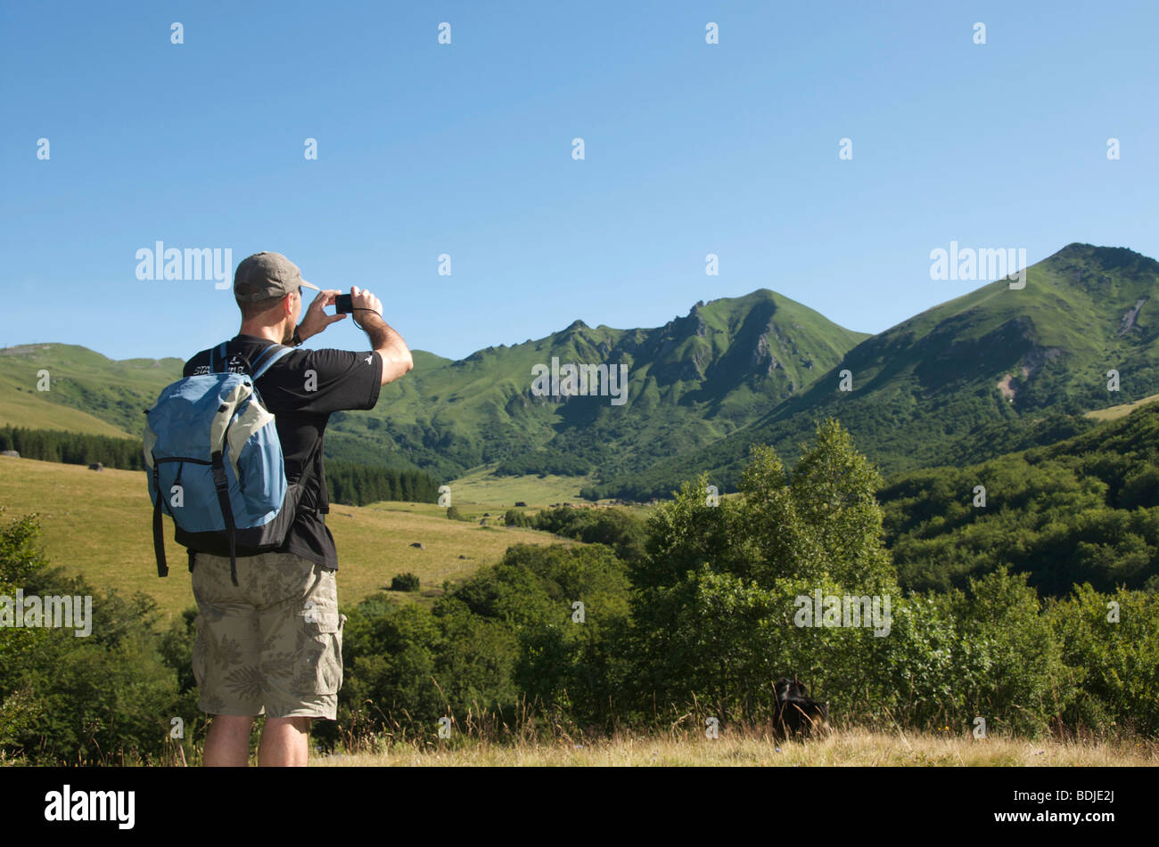 Hiker / walker in the Massif du Sancy, Auvergne, France - taking a photo of the landscape. - Stock Image