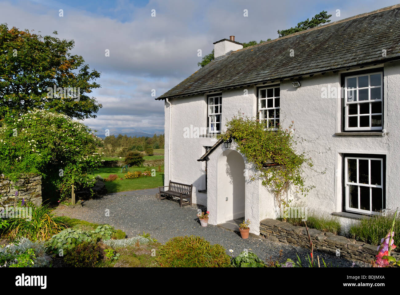 A Typical whitewashed country cottage set in open countryside in the English Lake District Stock Photo